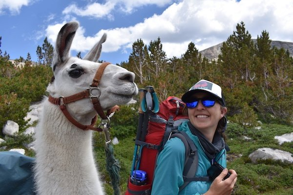 Smiling NOLS student backpacks beside a pack llama in the Wind River Range