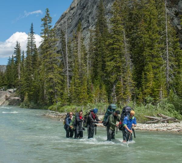 five NOLS participants cross river in Wyoming's Wind River Range
