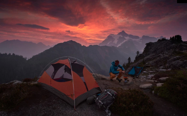 tent beside a man making a fire while camping in the mountains at sunset