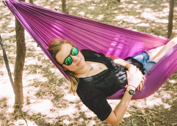 Kammok CEO and NOLS grad Haley Robison smiles for the camera in hammock