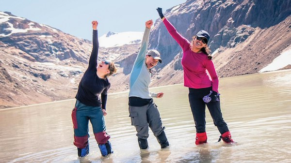 Three smiling NOLS participants stand in shallow mountain lake and raise arms in celebration