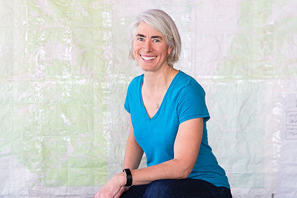 Portrait of Abby Warner, director of NOLS Teton Valley, with map in background