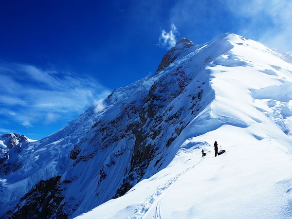NOLS Alaska students mountaineering on Denali with sun and blue skies over snowy-covered mountains