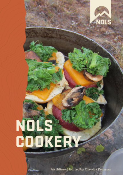 book cover of the NOLS Cookery, 7th edition, with picture of meal prepared on a NOLS course