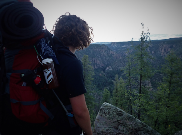 NOLS backpacking student pauses to enjoy a view of trees and mountains