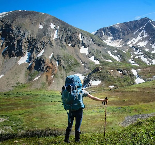NOLS student with backpack and trekking pole looks across a green valley toward snow-dotted mountains