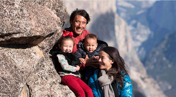 family of four with two young children smile together in the mountains