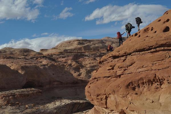 four NOLS students hiking in the Utah Canyonlands