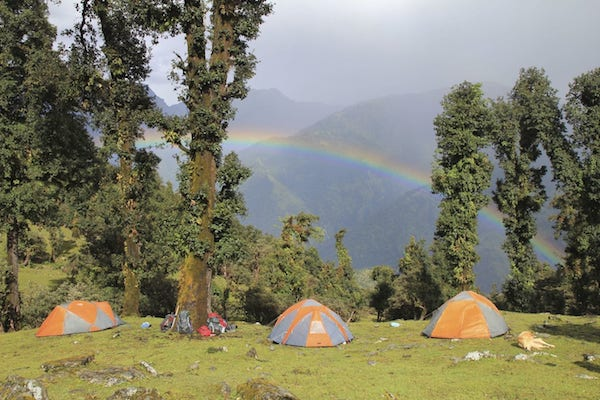 several tents set up in India's Pindari range with rainbow in background on NOLS backpacking course