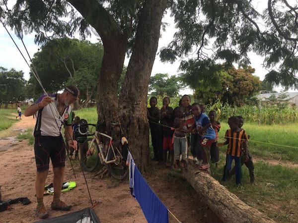 TDA cyclist on a bike tour pitches a tent near clothesline while group of children watches