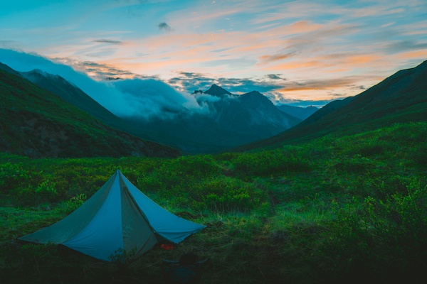 NOLS tent pitched in lush green valley in Alaska with sunset over mountains draped in clouds