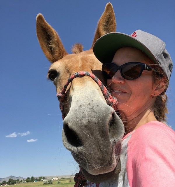 woman wearing baseball cap and sunglasses with her mule