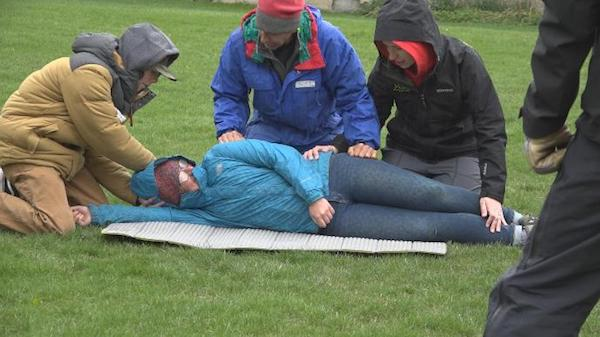 "three Wilderness First Aid students kneel beside a ""patient"" in a scenario"