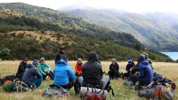 UVA business students sitting in a circle with backpacks in Patagonia with mountains surrounding