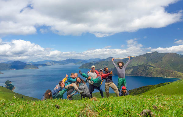 NOLS students pose for a group picture in New Zealand's mountains with blue water behind