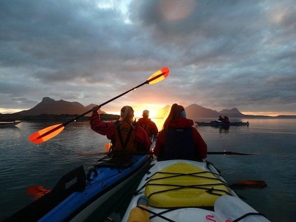 NOLS students paddle sea kayaks in Scandinavia at sunset