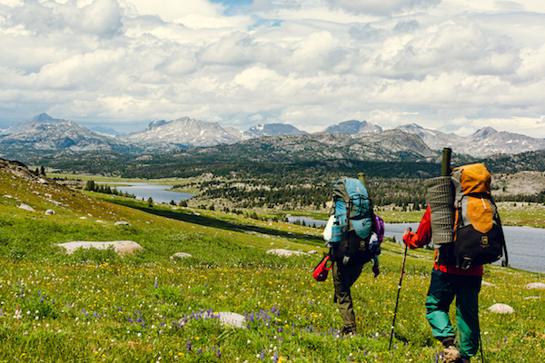 NOLS students hike past alpine lakes and wildflowers in Wyoming's Wind River Range