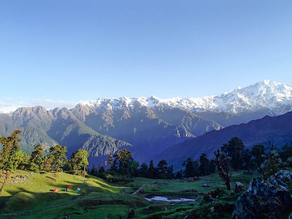 green valley in the Himalayas with NOLS tents and snow-capped mountains behind