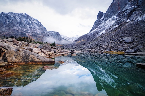 mountains and sky reflected in clear water in the Wind River Range