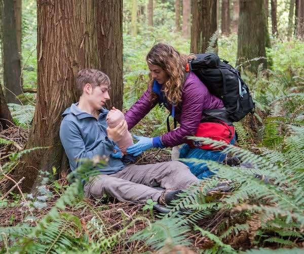 two NOLS Wilderness Medicine students practice their skills outdoors in a scenario