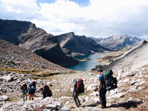 Five NOLS students descend a rocky slope toward alpine lakes in the Rockies