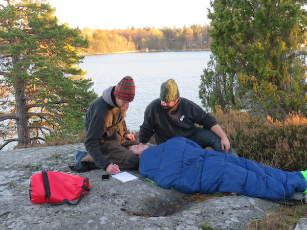 two NOLS Wilderness Medicine students practice caring for a patient lying in sleeping bag with lake and trees behind