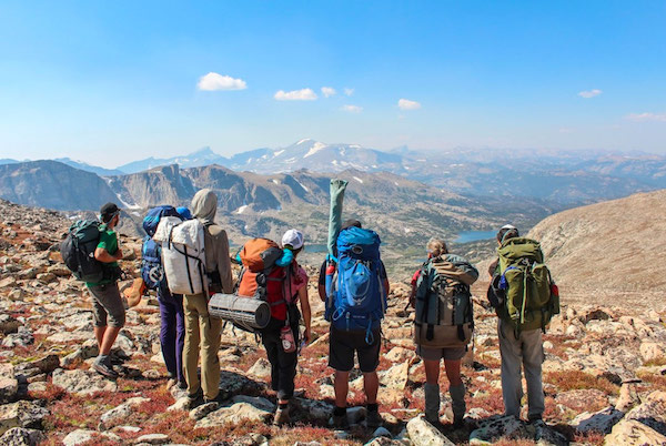 seven NOLS participants backpacking in Wyoming's Wind River Range look out at a view of lakes and mountains