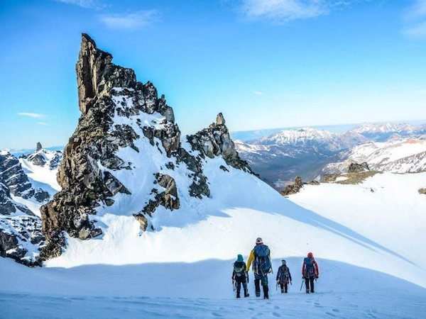 four NOLS participants trek across a snowfield toward crag in Patagonia's mountains