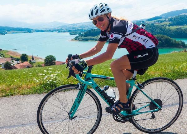smiling cyclist rides road bike in Europe on Ciclismo Classico trip