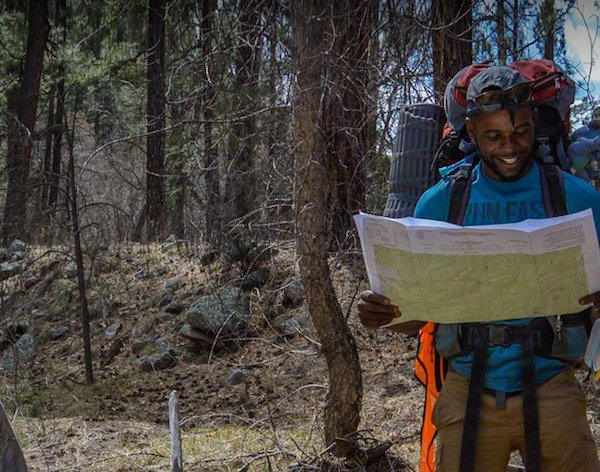 smiling NOLS student consults a map in the Southwest while backpacking