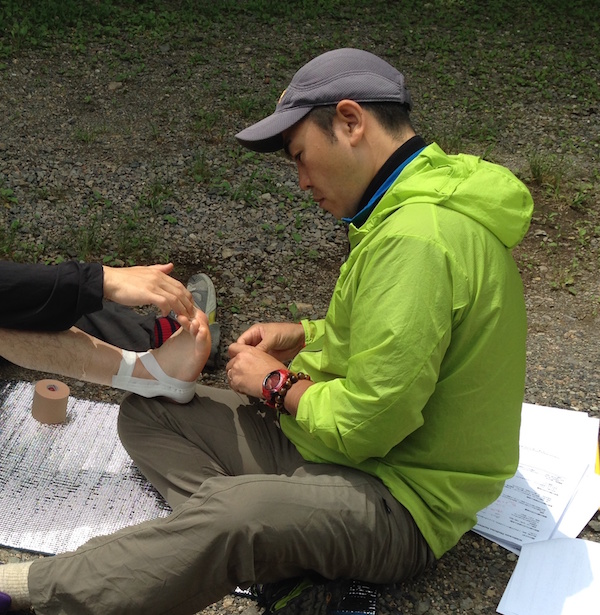 NOLS Wilderness Medicine student practices caring for a patient's ankle during a scenario