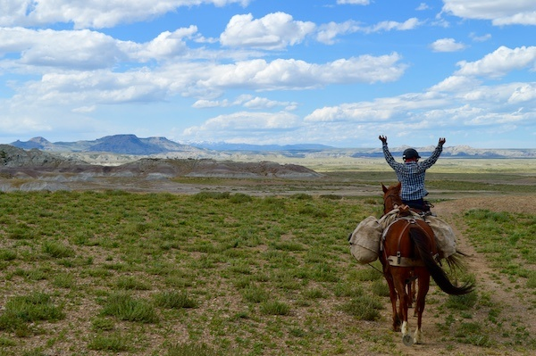 NOLS horsepacking student raises arms on horseback while traveling in the Wyoming backcountry