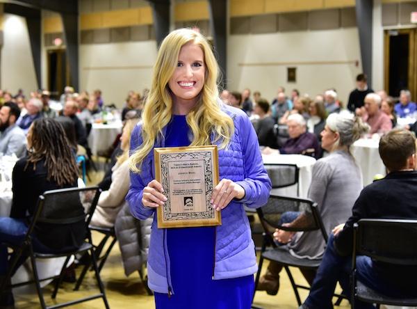 Jessica Wahl smiles while holding 2018 NOLS Stewardship Award