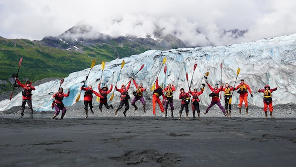 14 NOLS students holding kayak paddles jump for joy in front of an Alaskan glacier