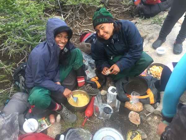 smiling C5 students smile while making backcountry mac and cheese on a NOLS course