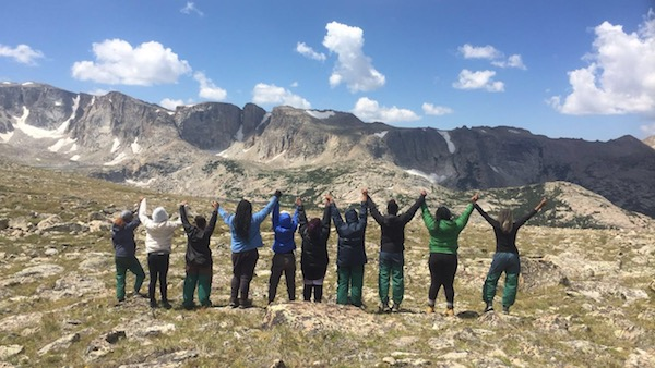 C5 students on a NOLS course in the Wind River Range hold hands with outstretched arms while looking out at the mountains